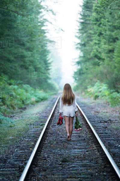 Teenage girl, walking along train track, holding red shoes and flowers, rear view Royalty-free stock photo