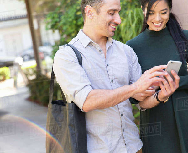 Couple in street looking at smartphone smiling Royalty-free stock photo