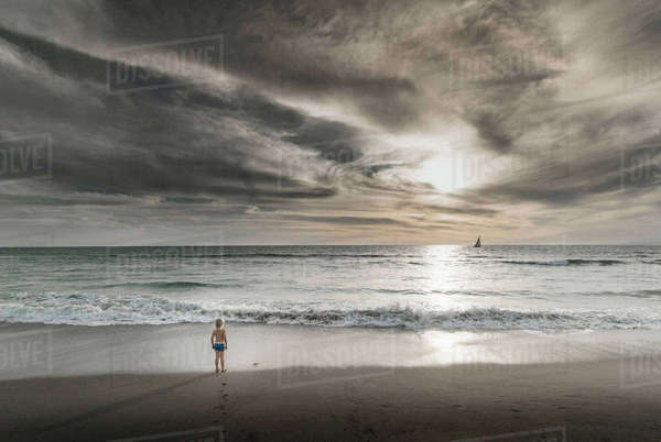 Boy looking out to sea and dramatic sky from Venice Beach, California, USA Royalty-free stock photo