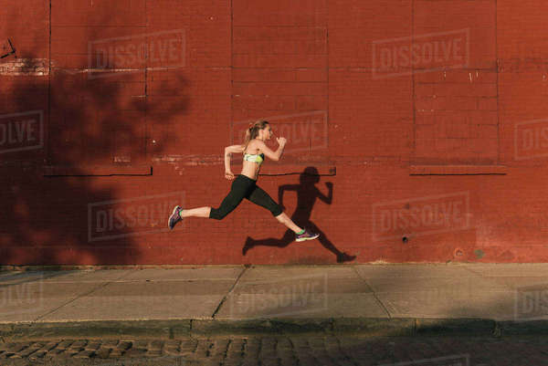 Young woman exercising outdoors, leaping through air, shadow beside her,  Brooklyn, New York, USA Royalty-free stock photo