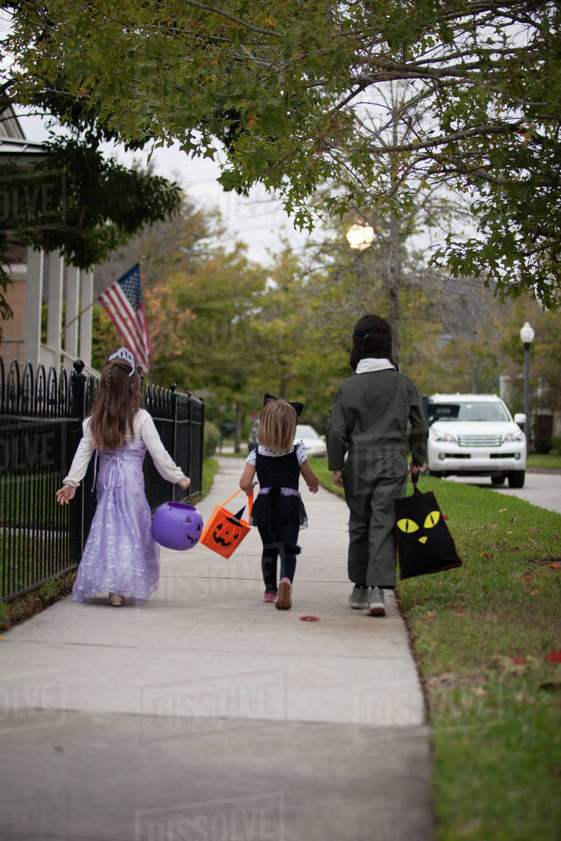 Rear view of boy and sisters trick or treating walking along sidewalk Royalty-free stock photo