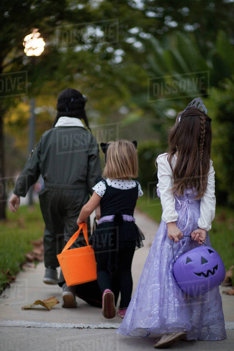 Rear view of boy and sisters trick or treating walking on sidewalk Royalty-free stock photo