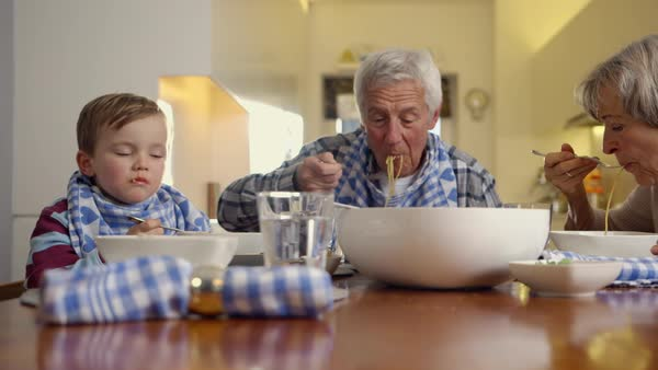 MS PAN SELECTIVE FOCUS Grandparents with child (4-5) eating spaghetti / Munich, Bavaria, Germany Royalty-free stock video