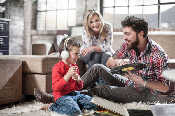 Parents showing vinyl record to son at home Royalty-free stock photo
