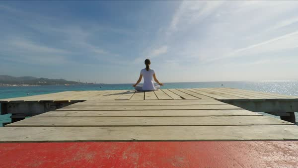 Wide shot of medium point-of-view shot of woman sitting on wooden pier meditating Royalty-free stock video