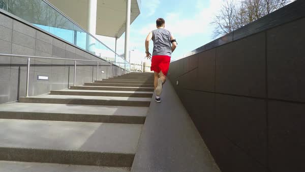 Wide to medium slow motion shot of man running by stairs Royalty-free stock video