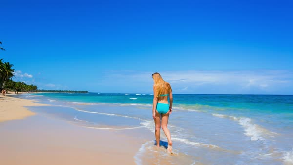 Wide shot of tilt shot young woman walking on beach Royalty-free stock video
