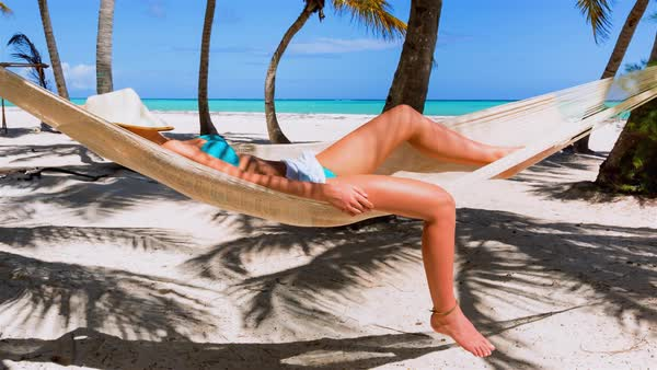 Woman lying in hammock with hat on face Royalty-free stock video