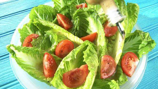 Putting salad dressing on romaine lettuce and tomato salad Royalty-free stock video