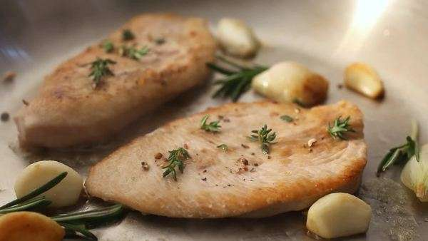 Turkey breast with garlic and herbs in a frying pan Rights-managed stock video