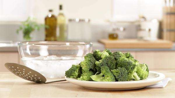 Broccoli florets, a slotted spoon and iced water (prepared for blanching) Rights-managed stock video