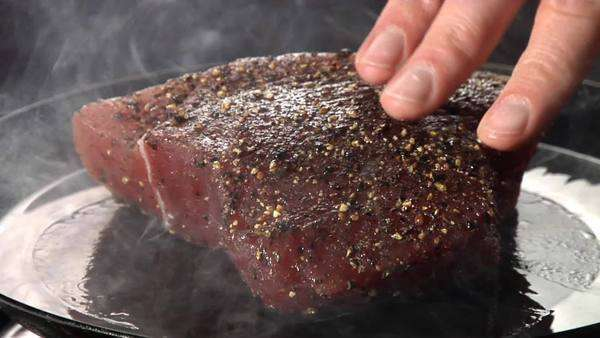 A tuna steak being placed in a hot pan Rights-managed stock video