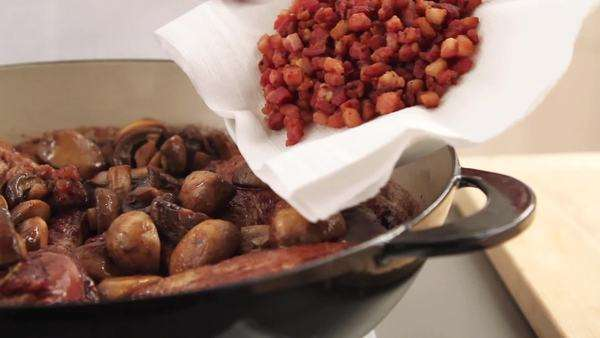 Fried bacon being added to coq au vin Royalty-free stock video