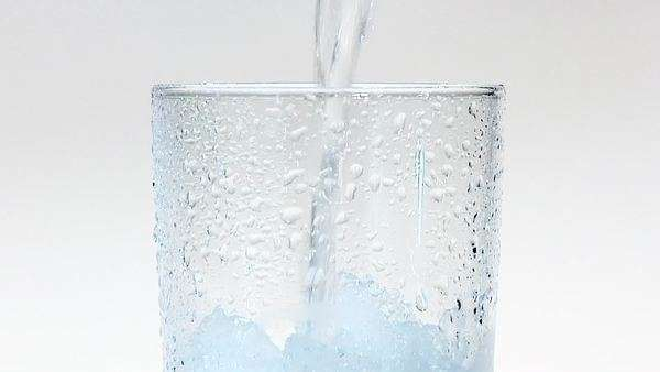 Pouring water into a glass of crushed ice (close-up) Royalty-free stock video
