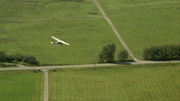 A small crop plane flying over Alberta farm land Royalty-free stock video