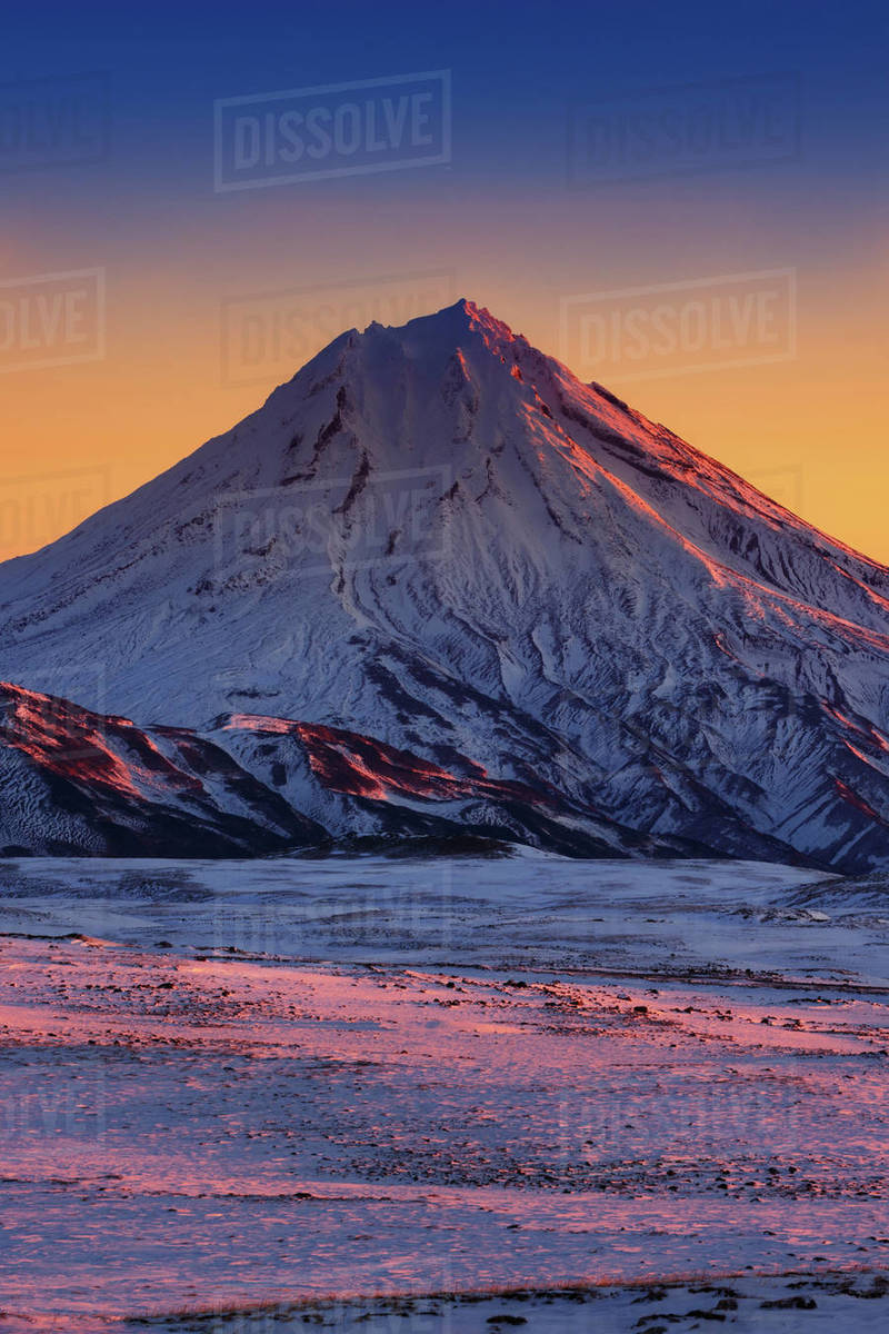 Winter volcanic landscape of Kamchatka Peninsula: stunning morning snowcapped cone Volcano Vilyuchinskay Sopka at sunrise, full daylight arrives, scenery yellow-blue sky on horizon. Russian Far East. Royalty-free stock photo
