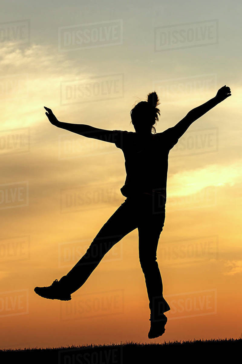 Silhouette of teen girl jumping for joy at sunset. Royalty-free stock photo