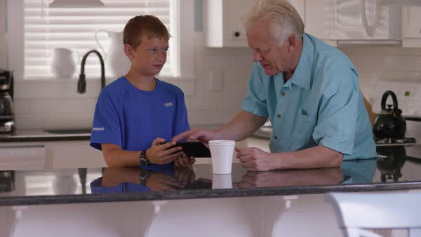 Grandson showing grandfather how to use tablet Royalty-free stock video