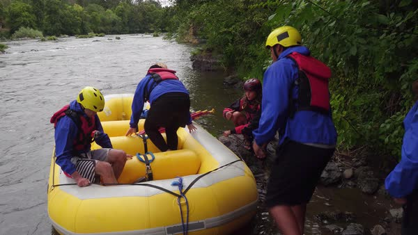 Group of people white water rafting getting into raft Royalty-free stock video