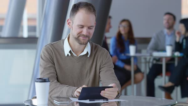 Young businessman using digital tablet in office lobby Royalty-free stock video