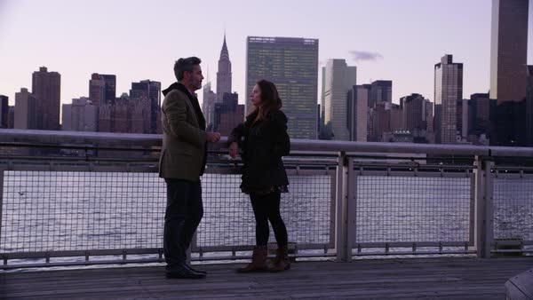 Couple in New York City stand by river talking with skyline in background Royalty-free stock video