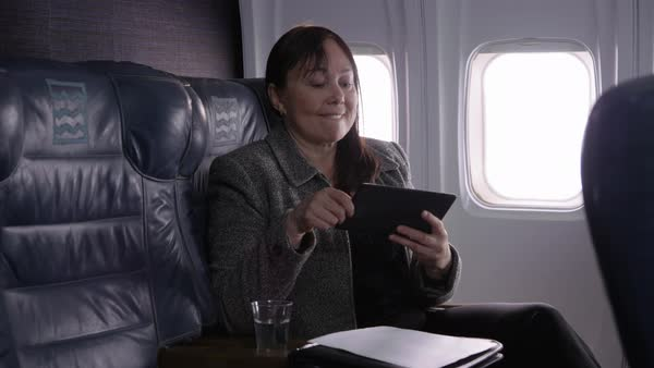 Businesswoman using digital tablet on airplane Royalty-free stock video
