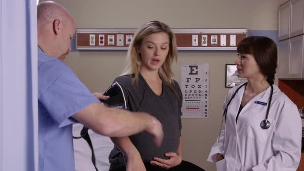 Pregnant woman gets checkup with doctor and nurse Royalty-free stock video