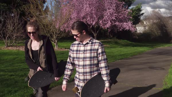 Two young people at park walking with skateboards Royalty-free stock video