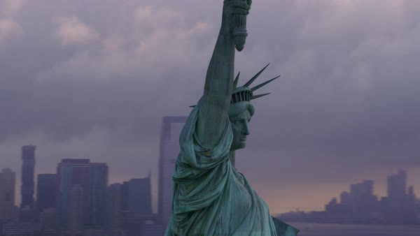Pull out from close-up of Statue of Liberty to reveal Manhattan and morning clouds.   Royalty-free stock video
