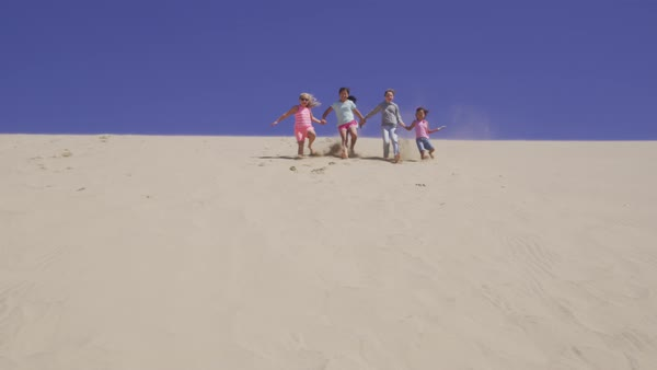 Group of kids running down sand dune at beach Royalty-free stock video