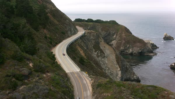 Highway One winds towards Bixby Creek Bridge along the Big Sur Coast in California.   Royalty-free stock video