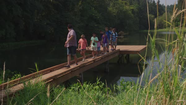 Kids at summer camp follow leader across dock Royalty-free stock video