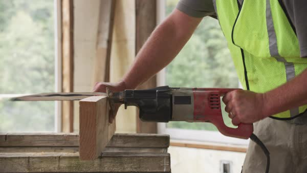 Construction worker cutting board with saw Royalty-free stock video