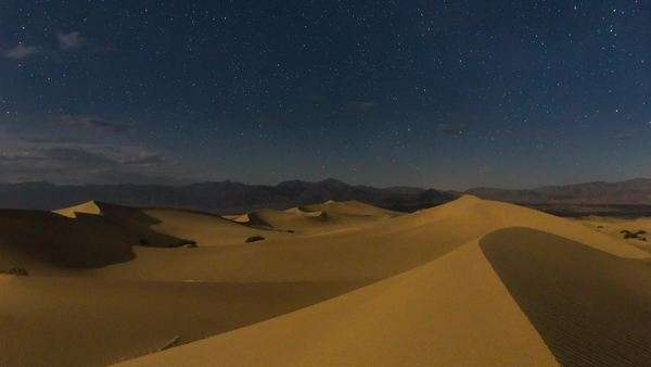 Stars at night with the desert lit in moonlight at Mystique Dunes in Death Valley California Royalty-free stock video