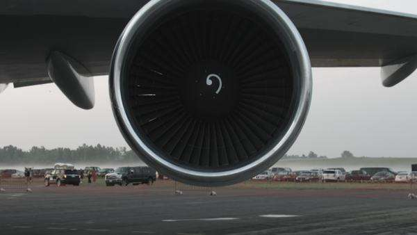 Tilt up from ground to a Boeing 747 jet engine, just before sunrise. Royalty-free stock video