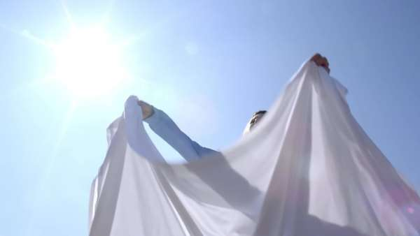 Medium shot of attractive brunette in a powder blue sweater, flipping out a clean white sheet on a sunny spring day. Low angle with sun and lens flare, looking up at sky. Slow motion, recorded at 180fps. Royalty-free stock video