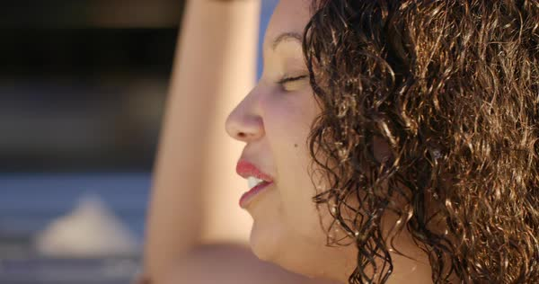 Big close up on young dark-skinned woman with wet hair, thinking to herself in warm sunlight at a resort location. Slow motion Royalty-free stock video