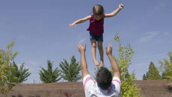 Dad throws his daughter up into the blue sky and catches her on a bright summer day Royalty-free stock video