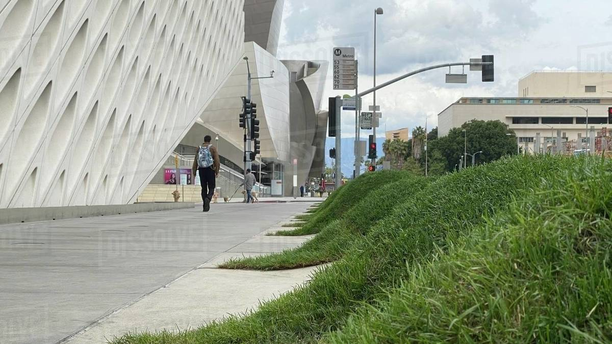 LOS ANGELES, CA, MAR 2020: people walking near The Broad museum and the Walt Disney Concert Hall in Downtown. Mountains visible in distance, bus stop and grass humps in foreground Royalty-free stock photo