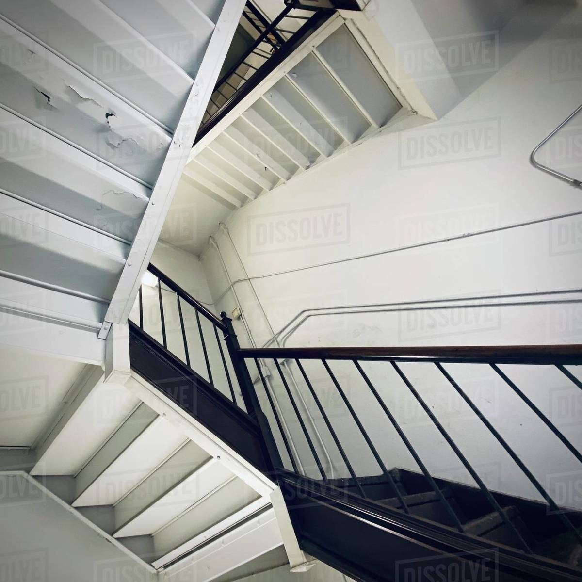 Interior staircase forms abstract pattern, similar to art by M C Escher, with unusual angle from underneath. Square composition Royalty-free stock photo