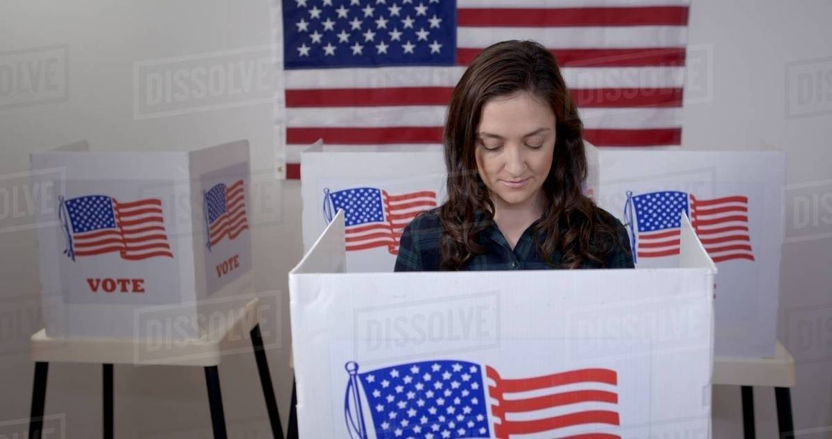 MS front view Caucasian American woman in plaid shirt in voting booth, casting vote at polling station. US flag on wall in background Royalty-free stock photo