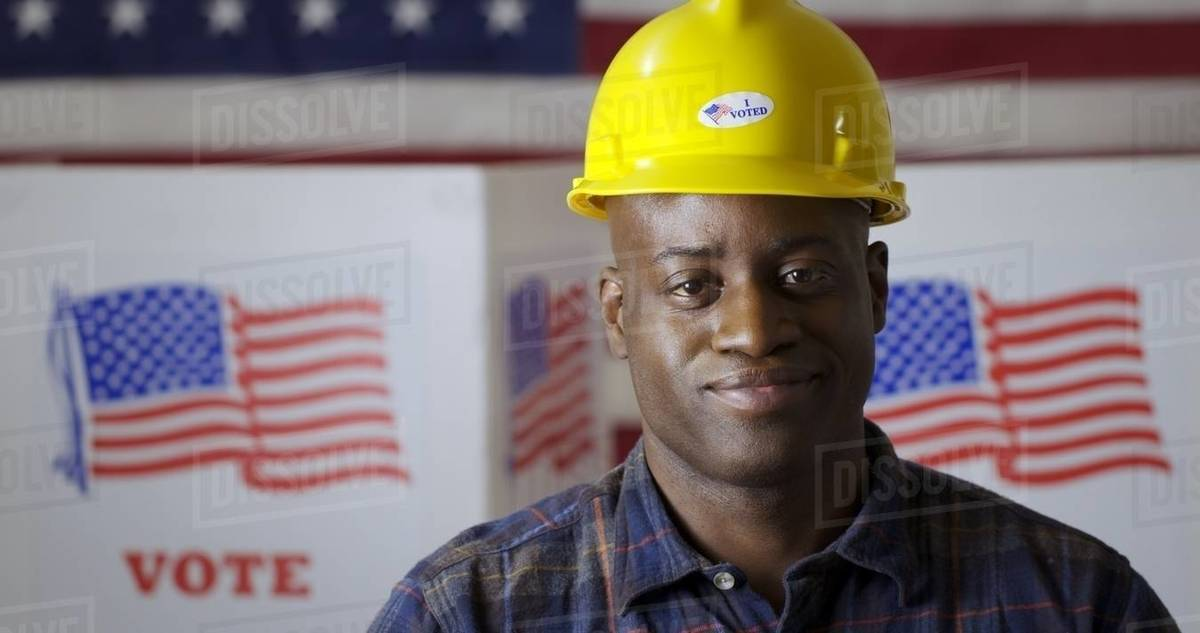 """Close up African American man in plaid shirt wearing hard hat with """"I Voted"""" sticker, facing camera and smiling in front of polling booths with US flag. Large US flag behind Royalty-free stock photo"""