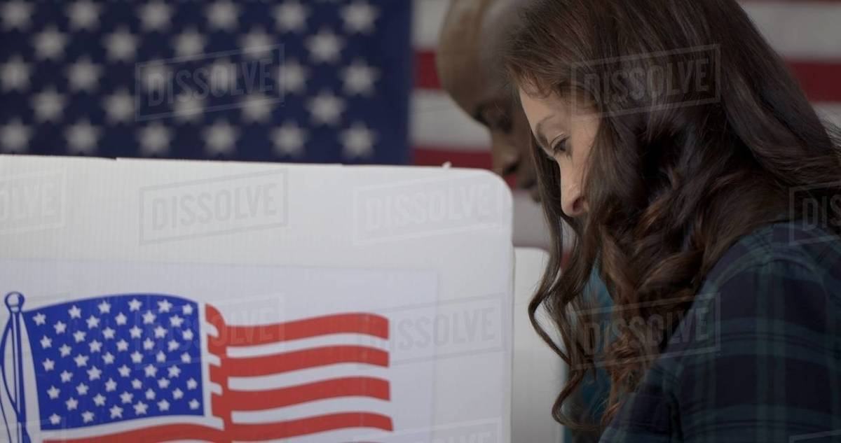 CU side view Caucasian woman, face hidden by hair, voting with African American man behind her in booths at polling station Royalty-free stock photo