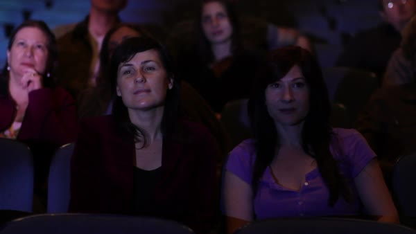 Various adults watching a movie and clapping.  Jib movement and projections on audience faces. Royalty-free stock video