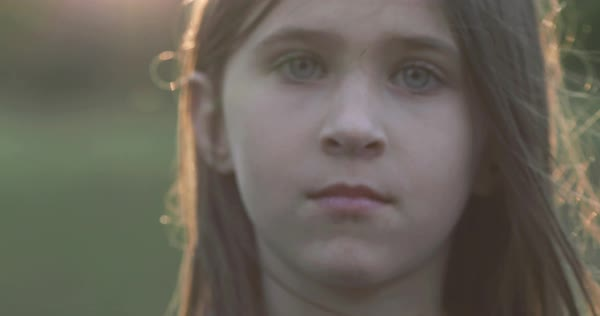 Hand-held shot of a girl looking at camera outdoors Royalty-free stock video