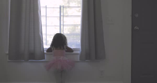 A little girl in a tutu looking out of a window Royalty-free stock video