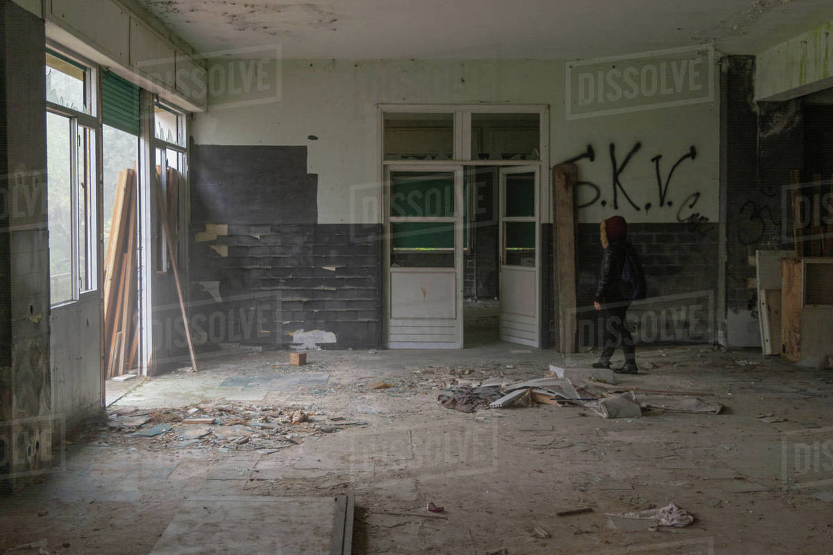 Old abandoned house decay hall with girl exploring it in the wood with scary fog from the door on the left Royalty-free stock photo