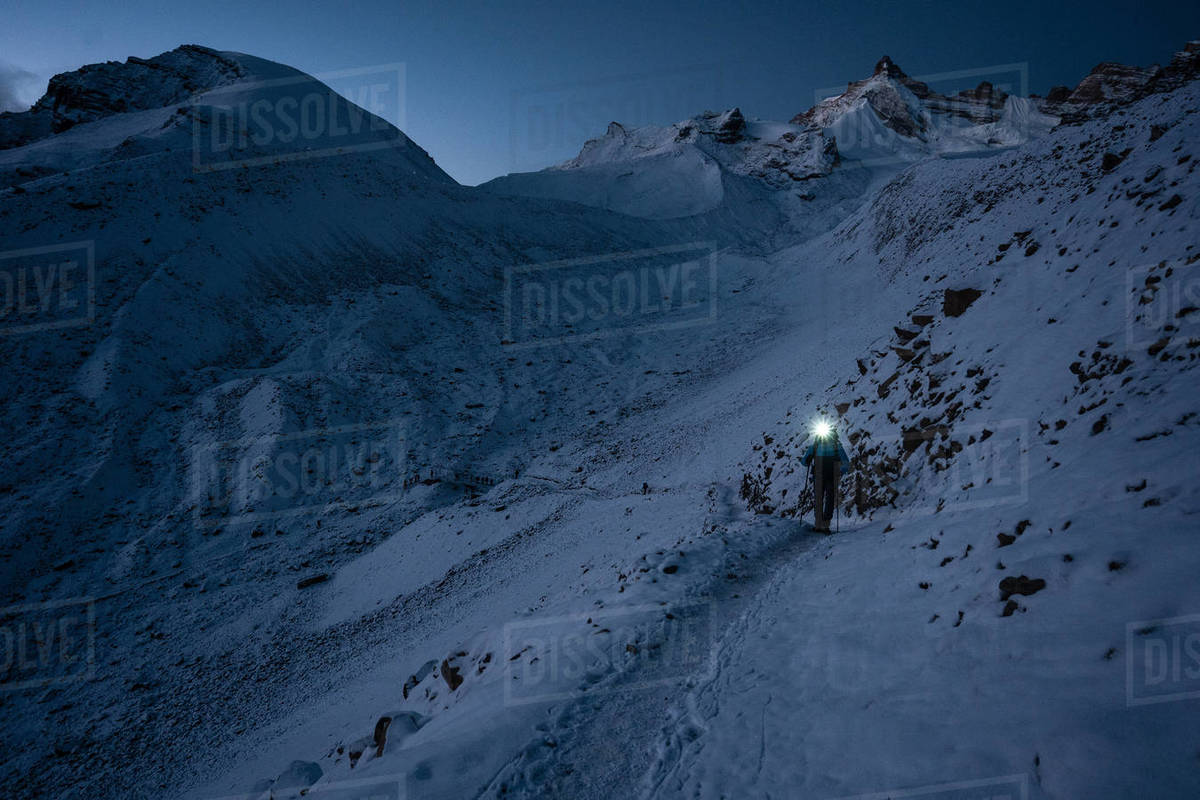Mountain trekker is ascending on the Thorong La Pass, Nepal, at early morning under night sky. Royalty-free stock photo