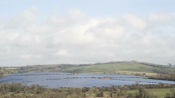 Timelapse of clouds passing over a solar farm in the rural landscape. Wales, UK. Rights-managed stock video