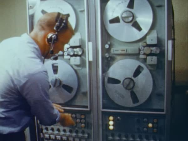 Computer engineer loading tape reels into a computer data reader and closing the cabinet doors. Rights-managed stock video